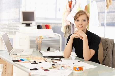 estilista: Retrato de atractivo dise�ador de moda femenina sentada en escritorio de la Oficina, sonriendo.