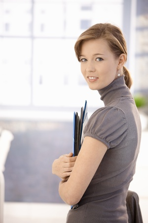 executive assistants: Profile portrait of attractive office worker, holding file folders. Looking at camera, smiling. Stock Photo