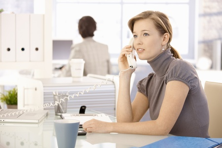 Office worker sitting at desk, talking on landline phone.
