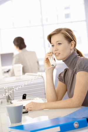 Young businesswoman sitting at office desk, talking on landline phone. photo