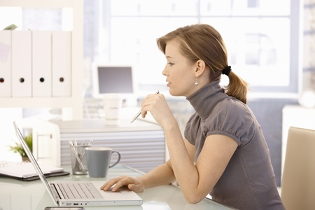 female office worker: Attractive office worker sitting at desk, using laptop computer, looking at screen. Side view.