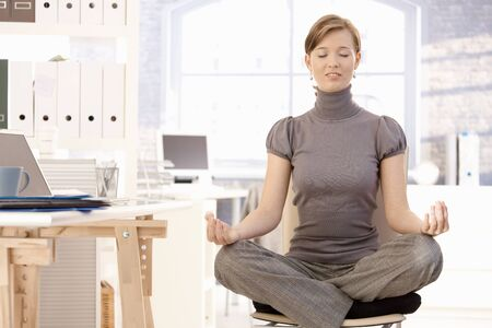 Attractive female office worker meditating photo