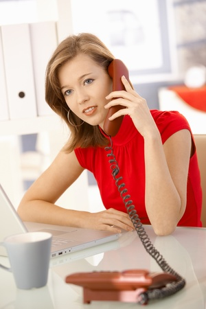 Young businesswoman sitting at office desk, talking on landline phone. Looking at camera. photo