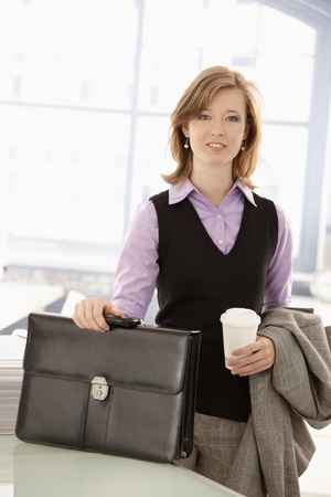 Young businesswoman arrived to office in the morning with coffee to go in hand. photo