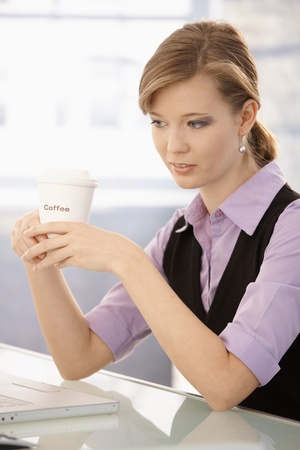 Portrait of young businesswoman sitting at office desk, drinking coffee. photo