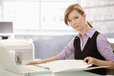 Office worker sitting at desk, doing paperwork. Looking at camera, smiling.