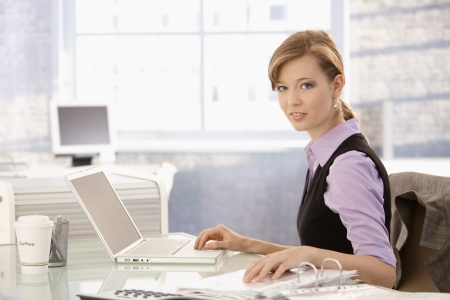 Young businesswoman working at desk, using laptop computer checking data on paper.
