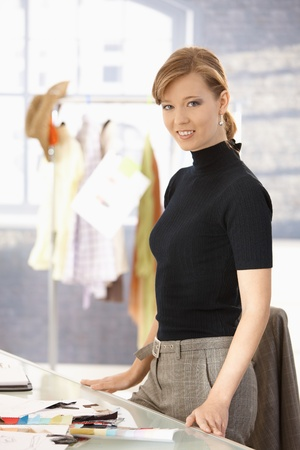 Young attractive female fashion designer standing at office desk, smiling. photo