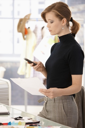 Young attractive female fashion designer standing at office desk, using mobile phone. photo