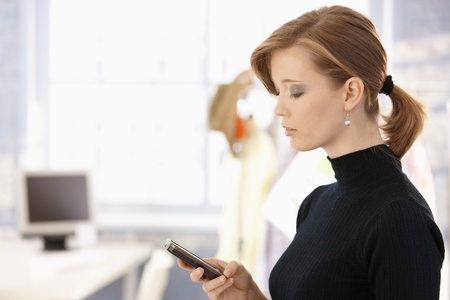 sms text: Profile portrait of young woman, using mobile phone in office.