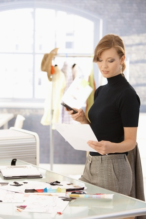 Young attractive female fashion designer working at office desk, using mobile phone, looking at paper. photo