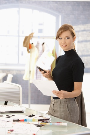office wear: Young attractive female fashion designer working at office desk, using mobile phone, looking at camera. Stock Photo