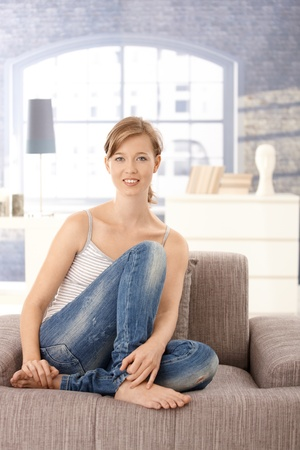 Portrait of young woman sitting on sofa at home, looking at camera, smiling. photo