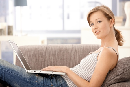 Young woman sitting on sofa at home, using laptop computer. Looking at camera, smiling. photo