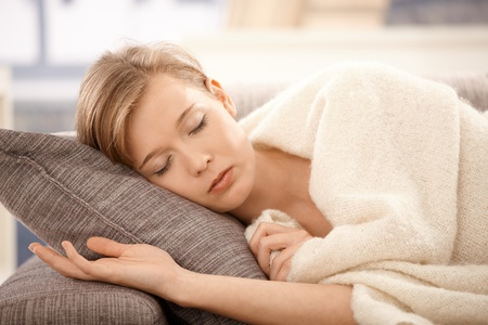 napping: Young woman sleeping on sofa at home, covered with blanket.