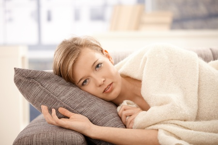 Young woman resting on sofa at home, covered with warm blanket. photo