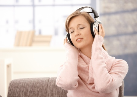Attractive young woman wearing pullover, listening music. photo
