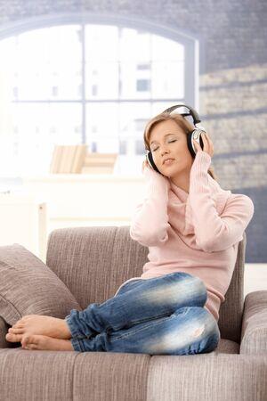 listening to music: Atractiva joven vistiendo chaqueta, escuchar m�sica en sof� en casa.