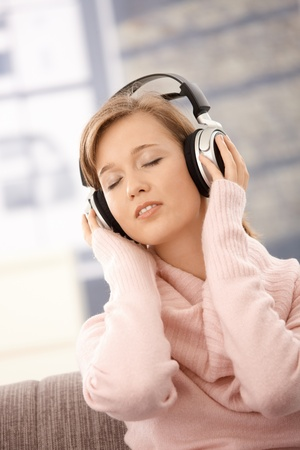 Attractive young woman wearing pullover, listening music on headphones with cosed eyes. photo