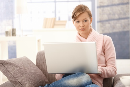 Attractive young woman wearing pullover, using laptop at home. photo