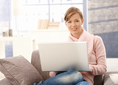 Young woman sitting on couch at home, browsing internet on laptop computer. photo