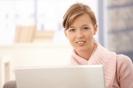 Closeup portrait of attractive young woman using laptop. photo