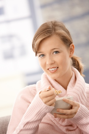 Closeup portrait of young woman sitting on having breakfast at home. photo