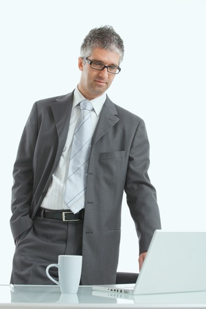 Serious businessman using laptop computer, standing behind office desk, looking down. Isolated on white. photo