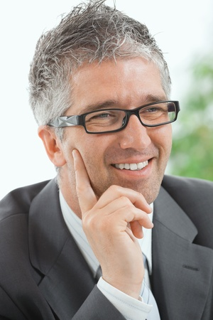 Closeup portrait of thinking businessman with grey hair, wearing grey suit and glasses. photo