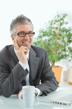 Businessman with grey hair, wearing grey suit and glasses thinking over laptop computer, sitting at desk, smiling. photo
