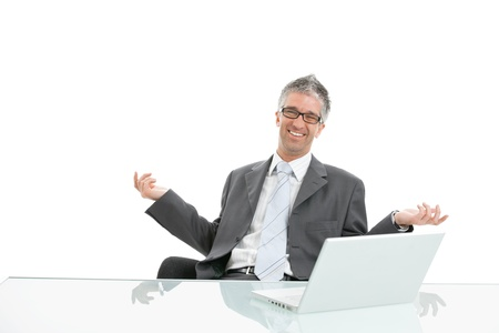 gratified: Happy businessman sitting at desk with raised arms, laughing. Isolated on white. Stock Photo