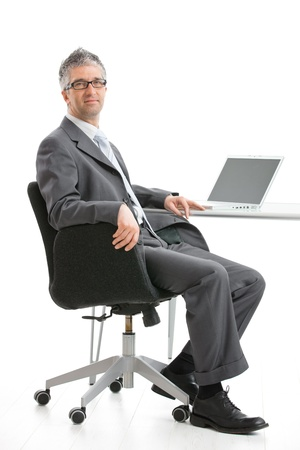 Businessman sitting at desk and working with laptop computer. Looking at camera, smiling. Isolated on white, copy space on screen. photo