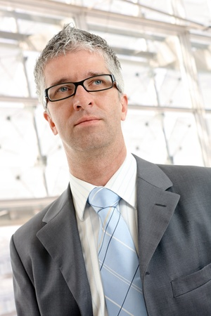 Closeup portrait of businessman wearing grey suit and glasses, in front of office building windows. photo