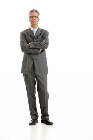 attire: Full length portrait of businessman wearing gray suit and glasses, standing with arms crossed.  Isolated on white background.