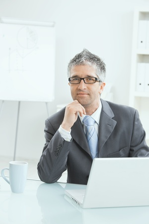 Relaxed businessman sitting on sofa, green office plant in background.  photo