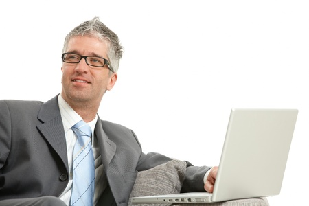Businessman wearing grey suit and glasses, sitting on couch with laptop computer, smiling. Isolated on white background. photo