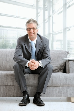trustworthy: Happy gray haired businessman sitting on couch in office lobby, looking at camera, smiling.