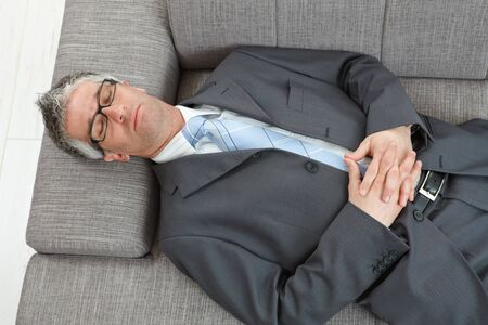 gray clothing: Tired businessman sleeping on couch, overhead shot. Stock Photo