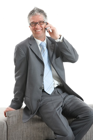 Businessman wearing grey suit and glasses, sitting on couch talking on mobile phone, smiling.  Isolated on white. photo