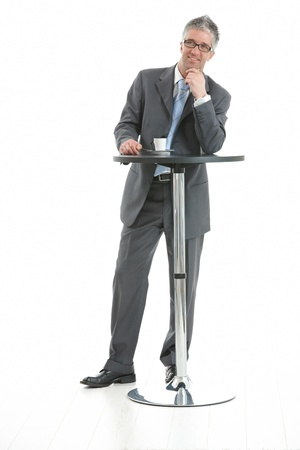 1 person only: Businessman standing at coffee table, leaning on hand, thinking. Isolated on white.