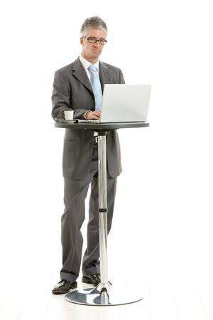 Businessman standing at coffee table, using laptop computer, looking at screen. Isolated on white. photo