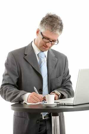 Businessman standing at coffee table, using laptop computer, writing notes. Isolated on white. photo