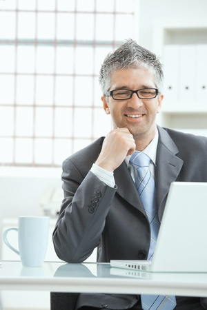 Businessman with gray heair thinking over laptop computer, sitting at desk, smiling. photo