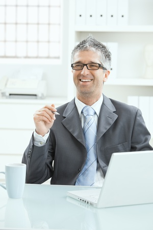 office wear: Businessman sitting at office desk working on laptop computer. Stock Photo