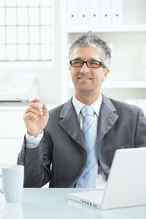 Businessman sitting at desk having a good idea, holding pen in hand, looking up smiling. Stock Photo - 8895292