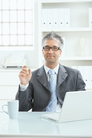 Businessman sitting at office desk working on laptop computer. photo