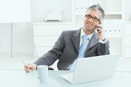 Gray haired executive businessman working on laptop computer at desk, in office, calling on mobile phone. photo