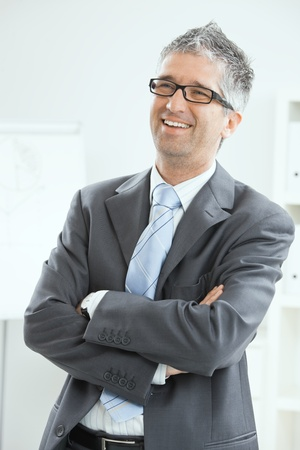 Happy businessman standing at office, smiling. photo