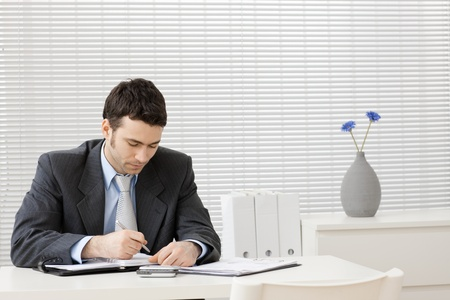 well read: Young businessman working at desk at office.