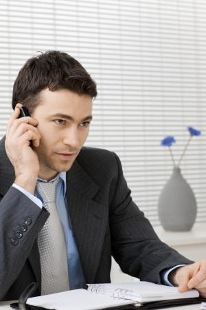 Businessman sitting at desk, listening his mobile phone. Imagens